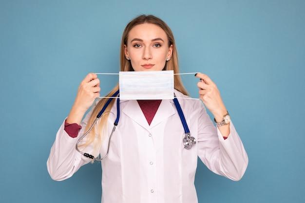 Ritratto di una giovane dottoressa che indossa una maschera protettiva su sfondo blu