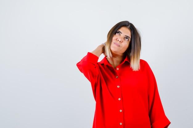Ritratto di giovane donna che tiene la mano sul collo in camicia rossa oversize e sembra una bella vista frontale