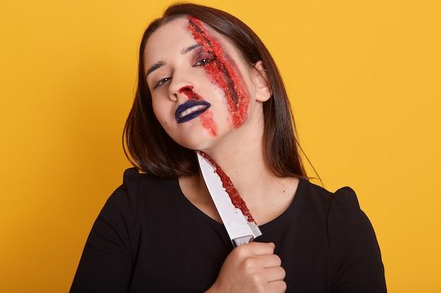 Ritratto di giovane assassino femmina con ferita insanguinata sul suo viso tenendo il coltello