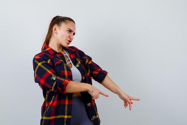 Ritratto di giovane donna che punta verso il basso in crop top, camicia a scacchi e guardando esitante vista frontale