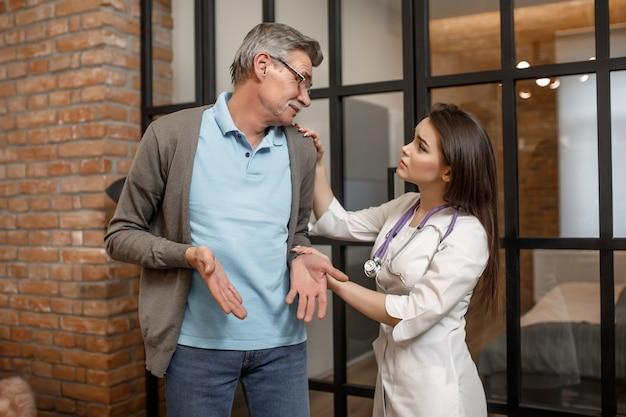 Ritratto di giovane donna, medico privato visita un uomo a casa e dà consigli per lui.