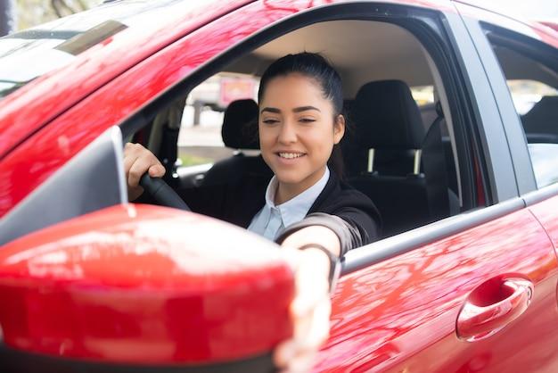 Ritratto di giovane pilota professionista femminile in un'auto e specchietto retrovisore in movimento. concetto di trasporto.