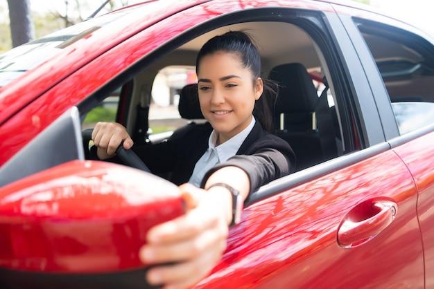 Ritratto di giovane pilota professionista femminile in una macchina e specchietto retrovisore in movimento.