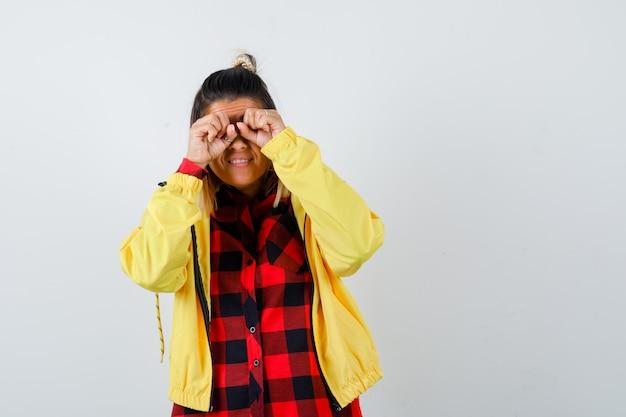 Ritratto di giovane donna che si sfrega gli occhi in camicia a scacchi, giacca e sembra una curiosa vista frontale