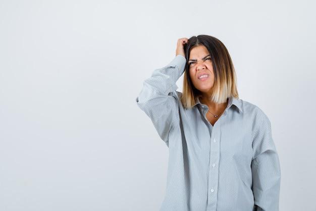 Ritratto di giovane donna che si gratta la testa con una maglietta sovradimensionata e che guarda pensierosa vista frontale