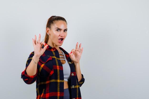 Ritratto di giovane donna che mostra gesto ok in crop top, camicia a scacchi e guardando felice vista frontale