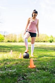 Ritratto di giovane calciatore femminile che corre intorno ai coni mentre si esercita con la palla sul campo.
