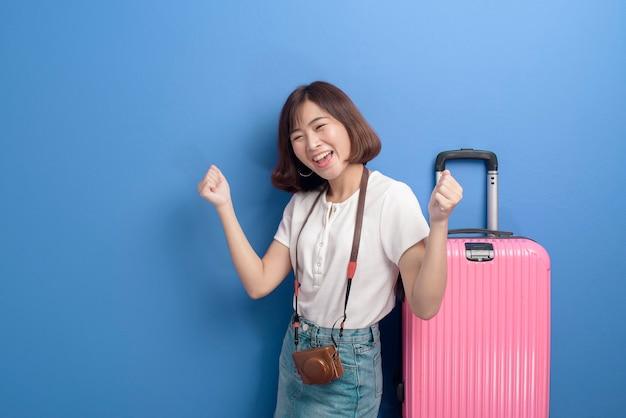 Un ritratto di giovane donna che viaggia isolato su sfondo viola in studio.