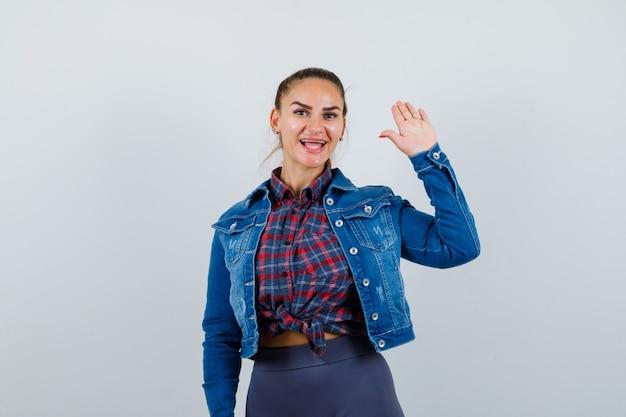 Ritratto di giovane donna che agita la mano per salutare in camicia a scacchi, giacca, pantaloni e guardando una bella vista frontale