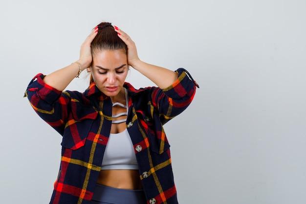 Ritratto di giovane donna con le mani sulla testa in top corto, camicia a scacchi e vista frontale stanca
