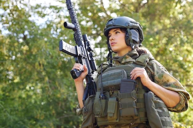 Ritratto di giovane donna con arma in abbigliamento militare all'aperto