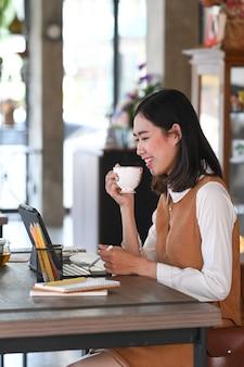 Ritratto di giovane donna che lavora con tablet computer e bere caffè caldo