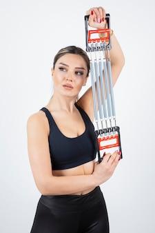 Ritratto di giovane donna in forma formazione con strumento palestra.