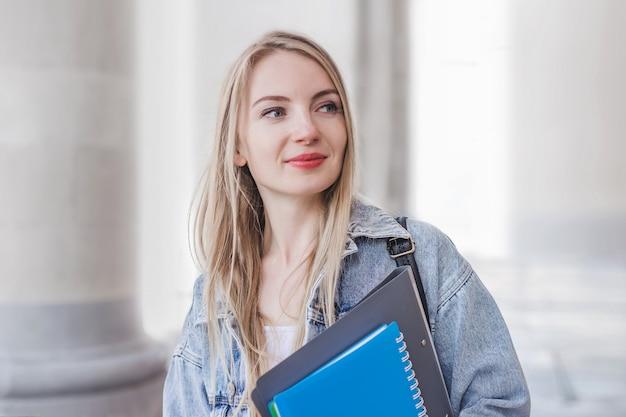 Ritratto di una giovane ragazza freelance che tiene una cartella del taccuino e in piedi dietro l'antico edificio