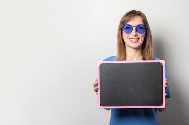 Ritratto di una giovane donna amichevole con un sorriso in una maglietta blu casual, occhiali blu, in possesso di una lavagna nera con spazio vuoto per il testo sulla luce. volto emotivo