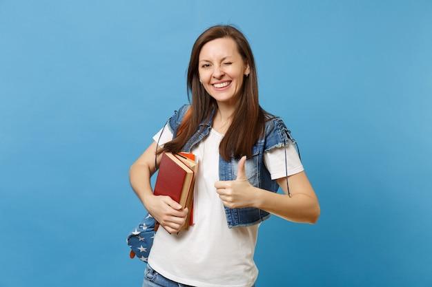 Il ritratto di giovane studentessa sveglia divertente in vestiti del denim con lo zaino che lampeggia mostrando pollice in su, tiene i libri di scuola isolati su fondo blu. istruzione nel concetto di college universitario di liceo.