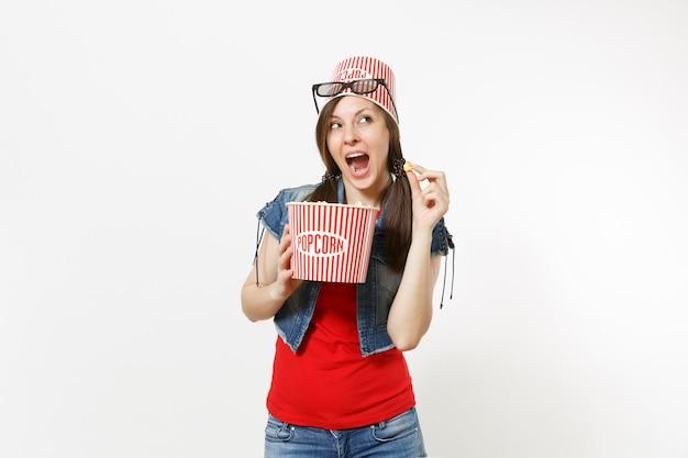 Ritratto di giovane donna graziosa divertente in occhiali 3d con secchio per popcorn sulla testa guardando film, mangiando popcorn dal secchio isolato su sfondo bianco. emozioni nel concetto di cinema.