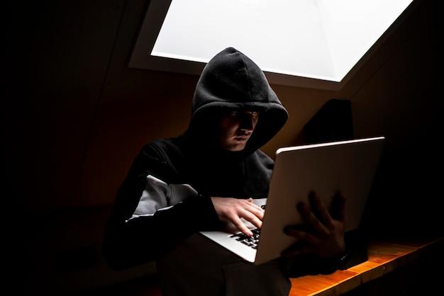 Ritratto di giovane geek in cappuccio in camera oscura con laptop