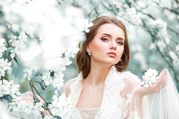 Ritratto di una giovane ragazza sullo sfondo di giardini fioriti. trucco naturale, acconciatura.
