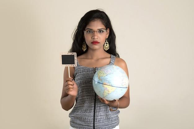 Ritratto di giovane ragazza che tiene e posa con un globo del mondo e un piccolo bordo nero