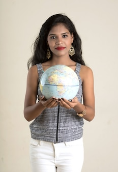 Ritratto di giovane ragazza che tiene e posa con un globo terrestre.