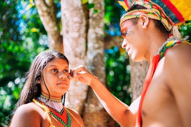 Ritratto di giovane ragazza etnia indigena pataxã³ facendo pittura del viso