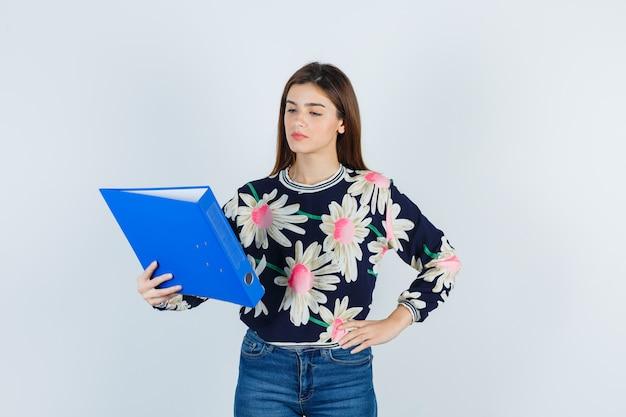 Ritratto di giovane ragazza che guarda la cartella, con la mano sulla vita in camicetta floreale, jeans e guardando premuroso, vista frontale.