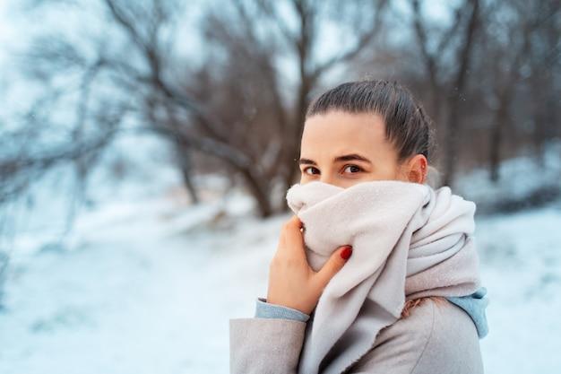 Ritratto di giovane ragazza nel parco in giornata invernale, indossa una sciarpa, sullo sfondo di alberi sfocati.