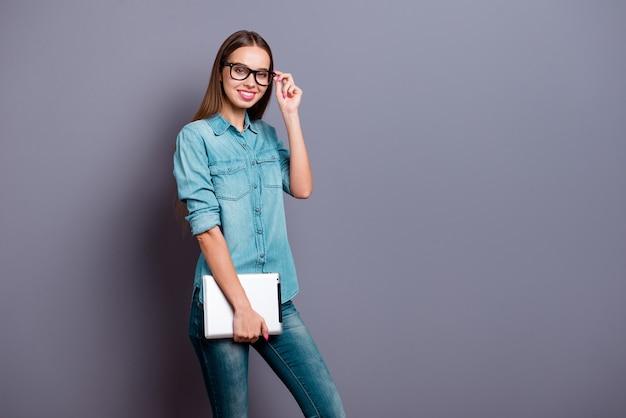 Ritratto di giovane ragazza in posa contro un muro grigio
