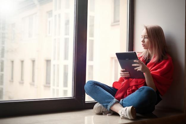 Ritratto di una giovane ragazza che legge un e-book.