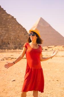 Ritratto di una giovane ragazza in abito rosso presso la piramide di cheope, la piramide più grande. le piramidi di giza il più antico monumento funerario del mondo. nella città del cairo, in egitto