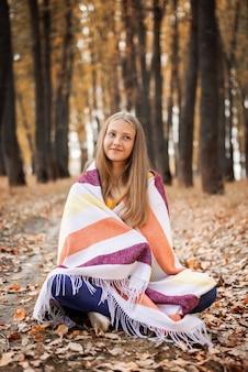 Ritratto di giovane ragazza seduta su foglie d'oro nel parco autunnale e guardando la telecamera