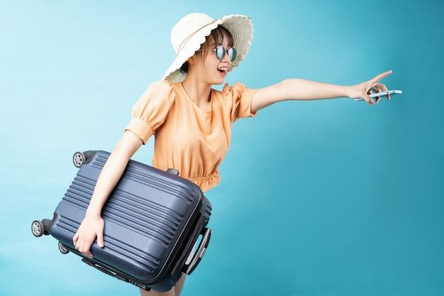 Ritratto di giovane ragazza che viaggia su sfondo blu