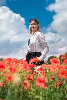 Ritratto di giovane ragazza che cammina nel campo di papaveri nel periodo estivo. godi la natura