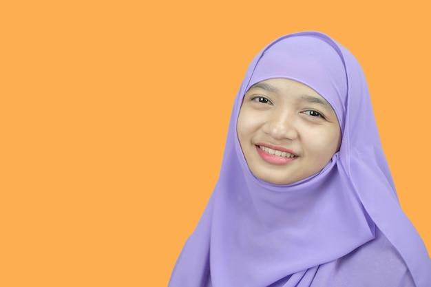 Ritratto giovane ragazza indossare hijab viola su sfondo arancione.