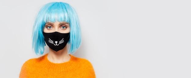 Ritratto di giovane ragazza che indossa maschera medica nera contro il coronavirus sul muro bianco con copia spazio.