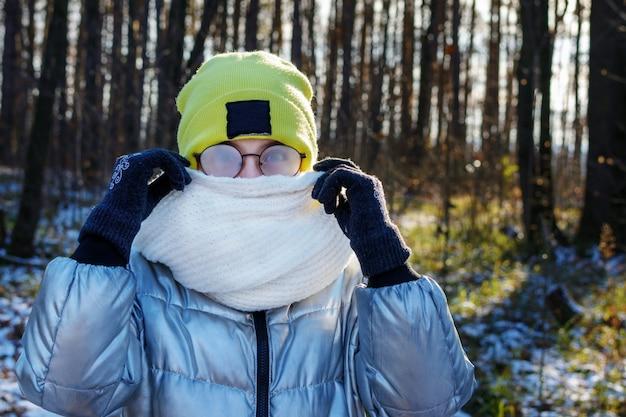 Ritratto di giovane ragazza che indossa sciarpa invece di maschera protettiva e problemi con gli occhiali appannamento dalla respirazione.