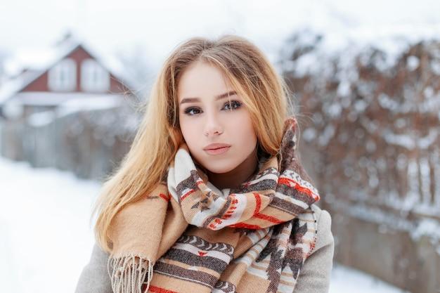 Ritratto di una giovane ragazza con belle labbra con gli occhi marroni in una sciarpa vintage elegante di lana in un cappotto grigio sulla strada del villaggio in una giornata invernale. ragazza carina alla moda.