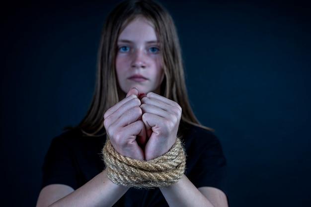 Ritratto di giovane ragazza con le mani legate su sfondo nero. avvicinamento