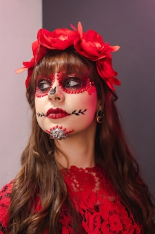 Ritratto di una giovane ragazza con il trucco dia de los muertos che guarda a sinistra.