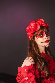 Ritratto di una giovane ragazza con il trucco dia de los muertos con copia spazio.