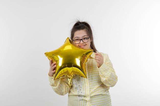 Ritratto di giovane ragazza con una sindrome di down che indossa una camicia a scacchi gialla che tiene il pallone ad aria a forma di stella