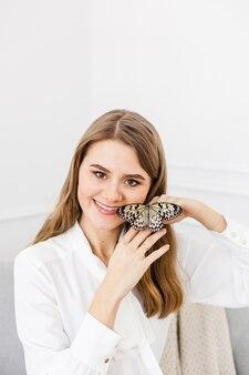 Ritratto di una giovane ragazza con i capelli lunghi che tiene una bella farfalla luminosa sulla sua mano