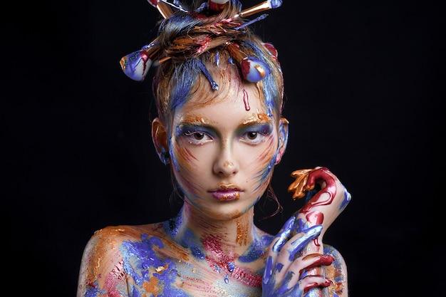 Ritratto di una giovane ragazza con trucco creativo multicolore su fondo nero
