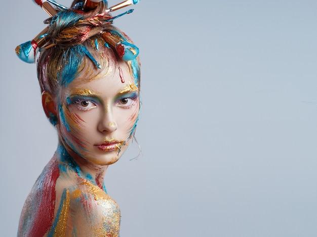 Ritratto di una giovane ragazza con trucco creativo multicolor su grigio