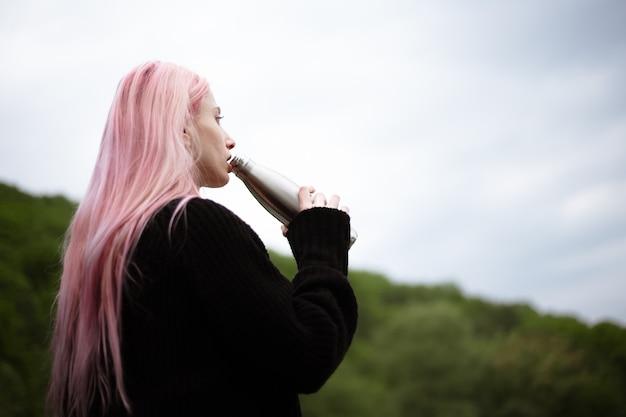 Ritratto di giovane ragazza con i capelli rosa acqua potabile dalla bottiglia termica in acciaio.