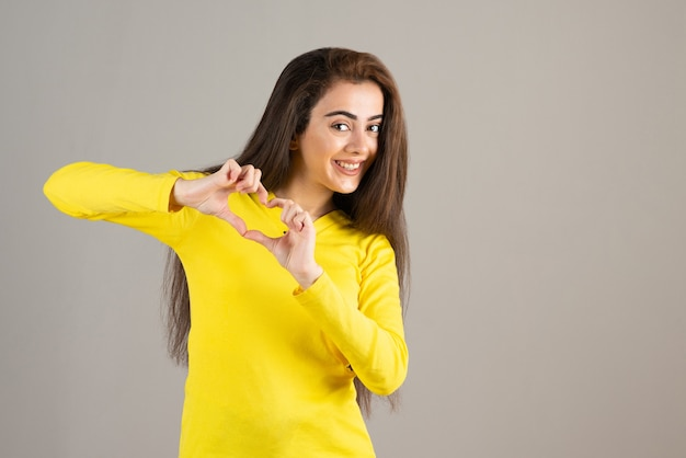 Ritratto di giovane ragazza in giallo in alto guardando e sorridente sul muro grigio.