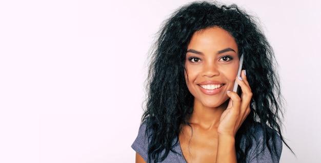 Ritratto di giovane e splendida ragazza afroamericana con i capelli corvini, sorridente di gioia mentre parla al telefono
