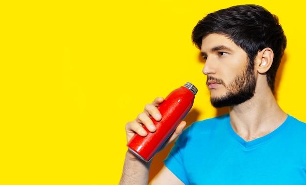 Ritratto di giovane ragazzo in camicia blu acqua potabile da bottiglia termica in acciaio riutilizzabile