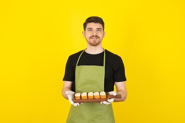 Ritratto di giovane ragazzo che tiene i rotoli di torta e che guarda l'obbiettivo.